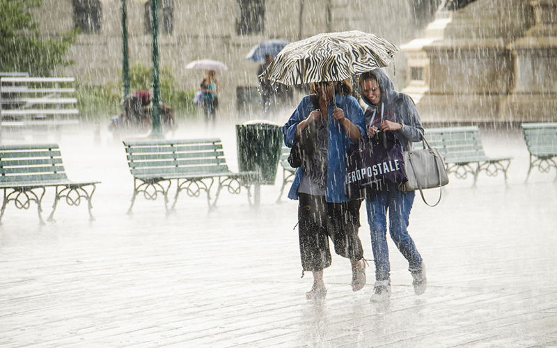 Quebec City, Canada - July 27, 2014: Two Women walk under umbrella during heavy rain in Quebec City, Canada, next to Chateau Frontenac.