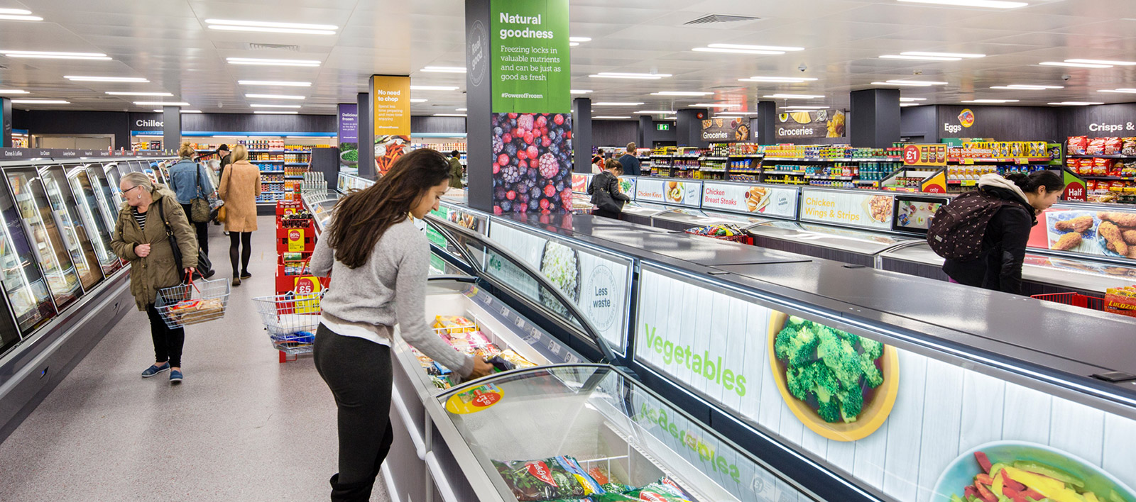 Lady picking up frozen food in Iceland supermarkets